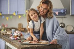 Pleased lady and child showing their culinary talent royalty free stock photo