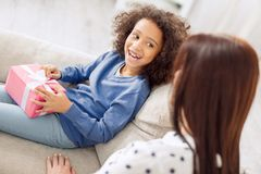 Pleased little girl holding her gift. Feeling delighted. Beautiful exuberant curly-haired girl smiling and holding her gift while looking at her mother sitting Royalty Free Stock Photos