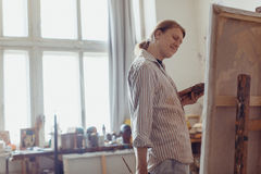 Pleased male artist drawing picture oil paints Royalty Free Stock Image