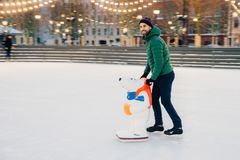 Pleased male skater being on skating ring, uses skate aid as tries to be in balance, looks happily aside, poses on ice. Cheerful royalty free stock image