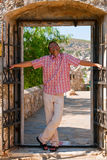 Pleased Man In Doorway. A pleased man standing in a doorway of old castle, with open arms Royalty Free Stock Photos