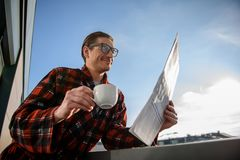 Pleased man enjoying coffee and journal on terrace. Low angle of satisfied adult male reading daily newspaper with glad smile, holding a cup in his hand. He is stock photography