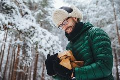 Pleased man in spectacles looks hapily at firewood which he log in winter forest, going to make fire, wears green anorak, poses ag. Ainst white winter forest royalty free stock image