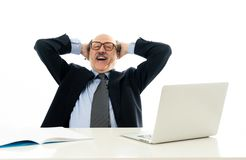 Pleased mature business man in his 60s working on laptop confident of success royalty free stock images