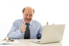 Pleased mature business man in his 60s working on laptop confident of success stock photography