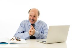Pleased mature business man in his 60s working on laptop confident of success royalty free stock image