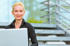 Pleased modern business woman using laptop Royalty Free Stock Image