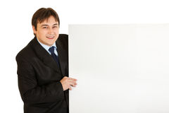 Pleased modern businessman holding blank billboard Royalty Free Stock Photography