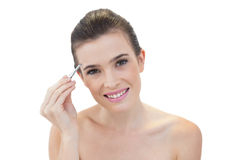 Pleased natural brown haired model plucking her eyebrows Royalty Free Stock Images