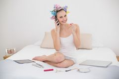 Pleased natural brown haired woman in hair curlers applying gloss while being on the phone Stock Photography