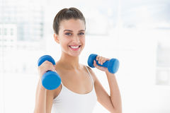 Pleased natural brown haired woman in white sportswear lifting dumbbells Royalty Free Stock Photos