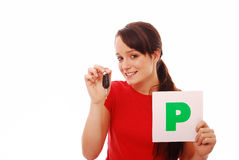 Pleased new driver. Smiling girl who has just passed test holding car key and P plate on white isolated background Stock Photo