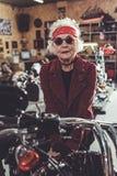 Pleased old woman bracing on bike Royalty Free Stock Photo