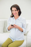 Pleased pregnant brown haired woman using her mobile phone Stock Image