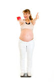 Pleased pregnant woman showing thumbs up Stock Photo