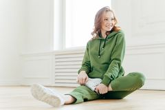 Pleased redhead woman focused aside, has happy expression, stretches legs, sits on floor, waits for instructor, wears hoody, white. Sneakers, has yoga stock images