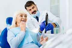Cheerful woman having a look at dentists work. Pleased with result. Smiling women expressing cheer while looking in the dental mirror and admiring her healthy Stock Photos
