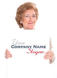 Pleased senior lady holding a vertical blank board Royalty Free Stock Photos