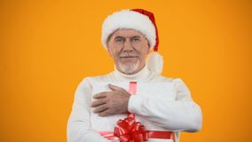 Pleased senior male in santa hat hugging giftbox, rejoicing new years surprise stock footage