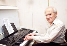 Pleased Senior Man Playing Piano Stock Photo