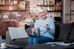 Pleased senior woman looking at counting stock images
