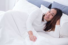 A pleased sleeping on the side young woman smiling softly in bed. The pleased sleeping on the side young woman smiling softly in bed Royalty Free Stock Images