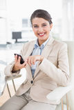 Pleased smart brown haired businesswoman using a mobile phone Royalty Free Stock Images