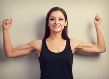Pleased strong fit woman showing muscle biceps with happy smilin Royalty Free Stock Photos