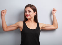 Pleased strong young woman showing muscle biceps with smiling on Royalty Free Stock Photos