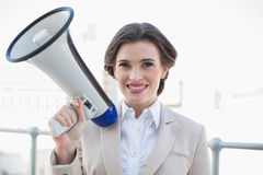Pleased stylish brown haired businesswoman holding a megaphone Royalty Free Stock Image