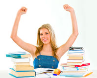 Pleased teengirl with raised hands sitting at desk Royalty Free Stock Photography