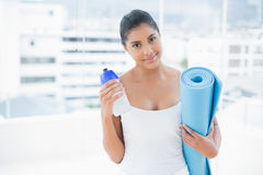 Pleased toned brunette holding sports bottle and exercise mat Stock Photos