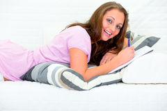 Pleased woman lying on couch and writing in diary Royalty Free Stock Photography