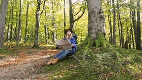 Pleased Woman with Map. Attractive, young woman in stylish, brown hat holding the map, feeling pleased after figured out the way, outdoor shot in green, fall stock video footage