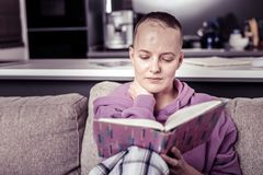 Pleased woman spending weekend at home with book. My hobby. Kind bold female expressing positivity while enjoying cozy weekend royalty free stock photos