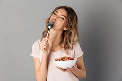 Pleased woman in t-shirt eating healthy food from plate. And looking at the camera over grey background royalty free stock photo