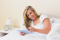 Pleased woman using a tablet pc lying on her bed Stock Photo