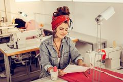 Cheerful designer looking at her sketches near the sewing machine. Pleased with work. Cheerful young designer sitting near the the sewing machine and looking at royalty free stock photo