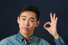 Pleased young Asian man giving okay sign Stock Photography