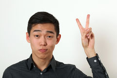 Pleased young Asian man giving the victory sign and looking at c Royalty Free Stock Image