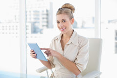Pleased young blonde businesswoman using a tablet pc Royalty Free Stock Photos