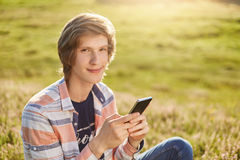 Pleased young boy with dark narrow eyes and stylish hair sitting at meadow holding cell phone checking his e-mail or reading news Royalty Free Stock Image