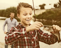 Pleased young boy holding on hook freshwater fish Royalty Free Stock Photography