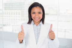 Pleased young dark haired businesswoman giving thumbs up Royalty Free Stock Images