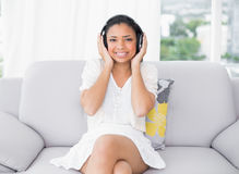 Pleased young dark haired woman in white clothes listening to music Royalty Free Stock Photos