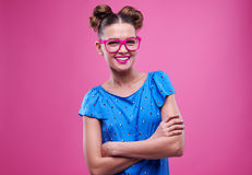 Pleased young girl in pink glasses crosses arms. Close-up of pleased trendy girl in pink glasses with crossed arms posing at the camera. Isolated over pink stock image