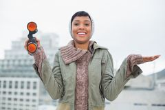 Pleased young model in winter clothes holding binoculars Royalty Free Stock Photography