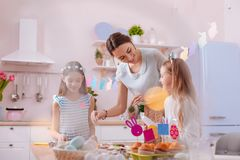 Pleased young woman talking to her kids. Pleasant conversation. Beautiful longhaired girls expressing positivity while spending time with their mom royalty free stock photo