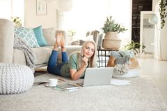 Pleased young woman using a laptop in living room royalty free stock photos