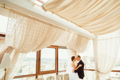 Pleasing bride and groom hug in the glass room.  royalty free stock photo